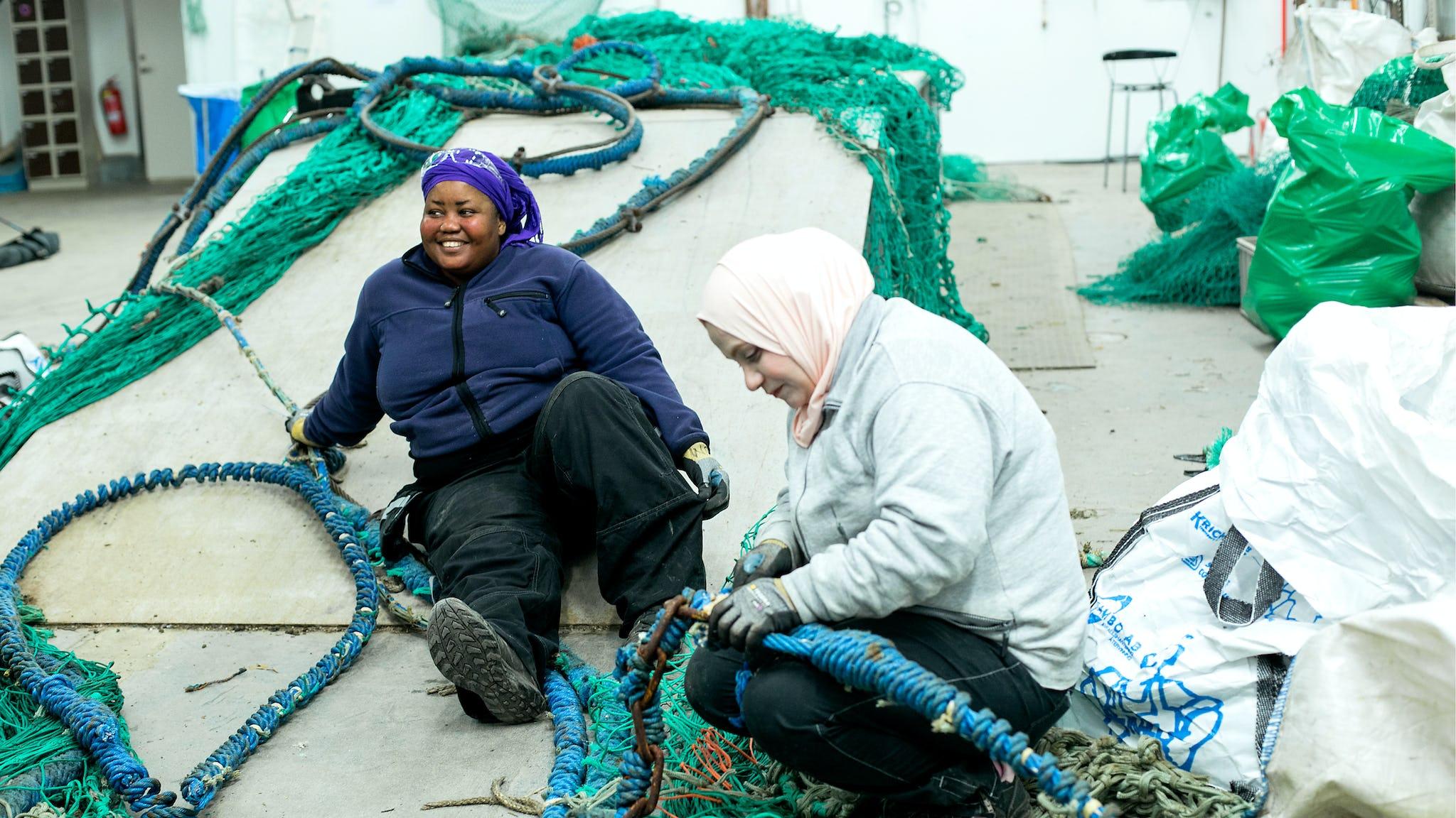 Djamila Moustapha och Waad Almallouhi rensar uttjänta fiskelinor från schackel och kättingar.