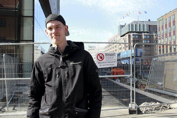 Claes framför en avspärrad byggarbetsplats