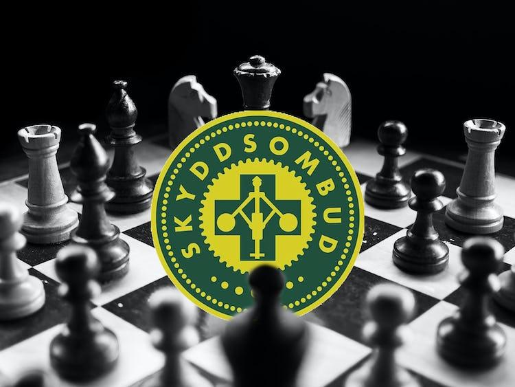 Ett schackbräde men skyddsombudsmärket i mitten