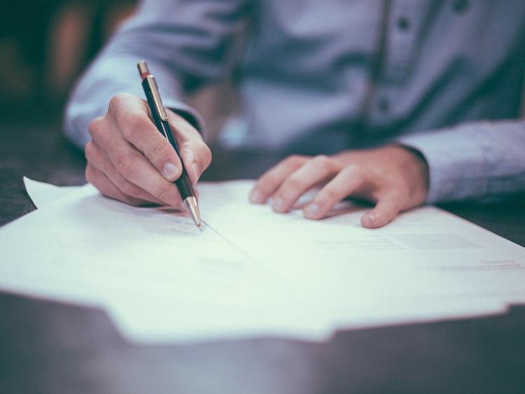 Överkroppen och händerna på en person som sitter vid ett bord och skriver med penna och papper.