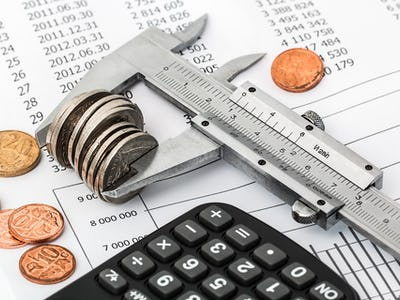 Ett skjutmått som mäter en traver mynt, invid en miniräknare och olika papper
