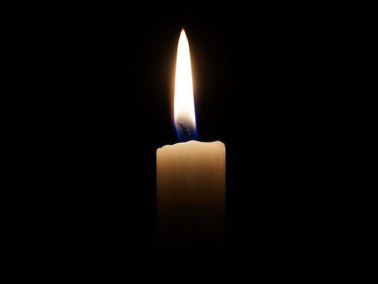 Ett brinnande stearinljus i mörkret