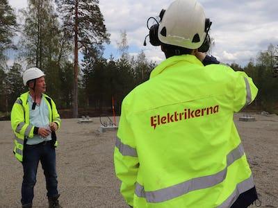 En person med Elektrikernas logga på jackan står på en arbetsplats