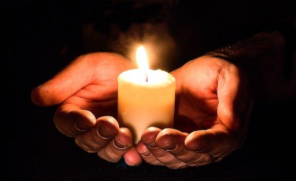 Ett stearinljus i två kupade händer