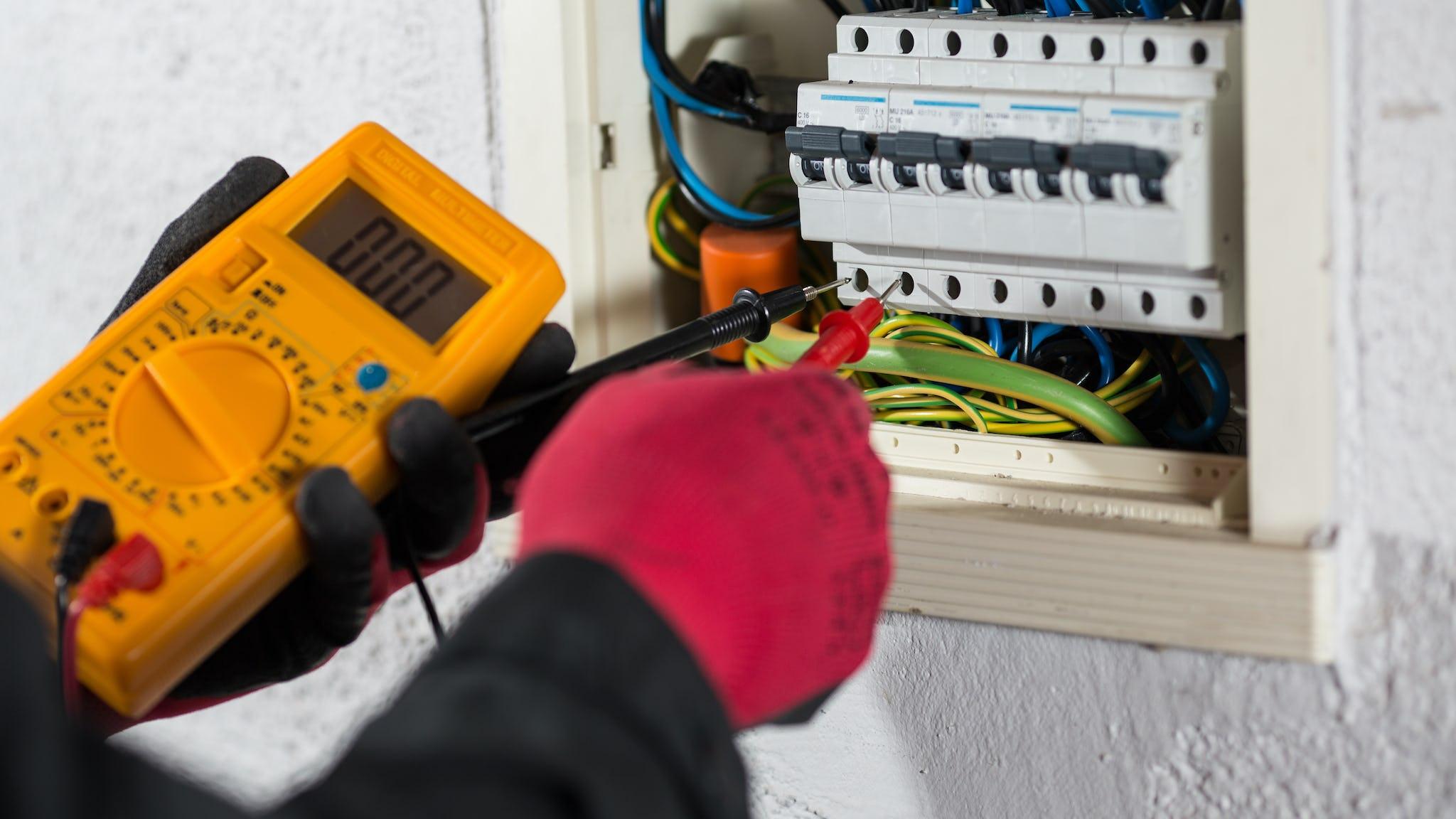 Händer som mäter spänningen i ett väggskåp.