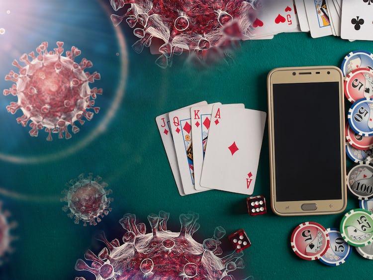 Ett spelbord med kort, marker och en mobiltelefon på, med bilder på det nya coronaviruset monterat över.