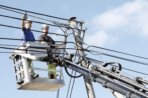Två personer arbetar med elledningar från en skylift