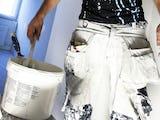 Nederkroppen på en person som bär en färghink. Benen är klädda i vita arbetsbyxor.