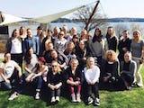Gruppbild på en stor grupp kvinnor på en gräsplan.