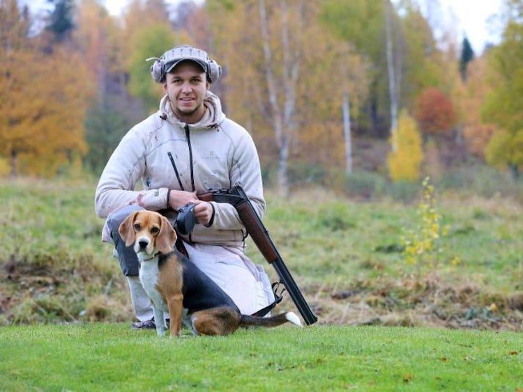 Emil Eriksson hållandes ett jaktgevär, och hans hund framför på marken