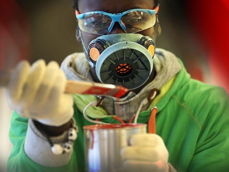 En person i skyddskläder arbetar med färg