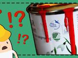 En tecknad person med bygghjälm tittar förskräckt på en färgburk med olika miljömärkningar på.
