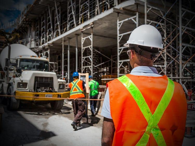 Ryggtavlan på en person i bygghjälm, som står och tittar på några andra personer som arbetar.