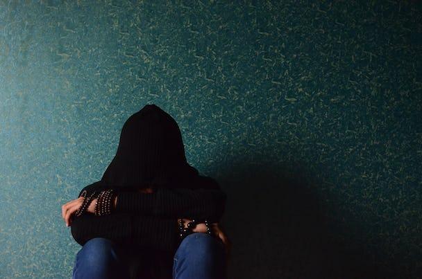 En person sitter med benen uppdragna vid en vägg
