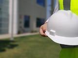 En person i gul reflexväst håller i en vit bygghjälm. I bakgrunden syns en byggnad.