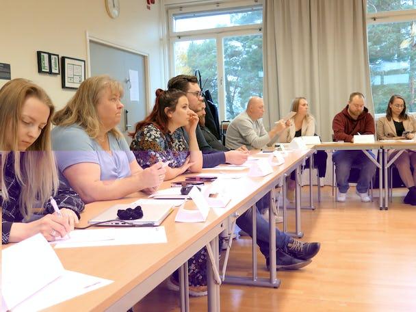 Ett antal personer vid ett långt mötesbord.