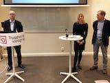 Tre personer står vid två talarbord framför en tom whiteboard. Ett av borden har en banderoll med LO:s logotyp på.
