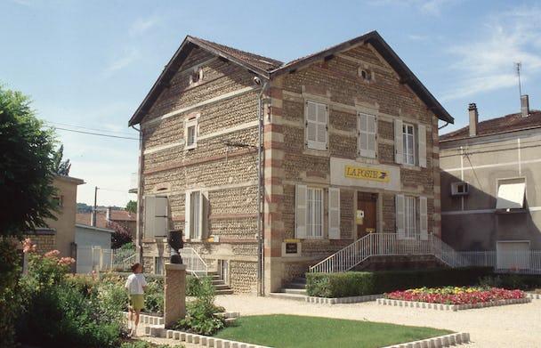 En brungrå, murad trevåningsvilla.
