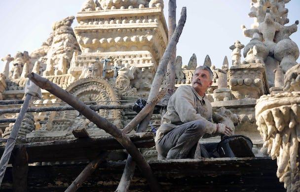 En man med säkerhetslina sitter på huk med händerna ovanför en hink, framför ett sandfärgat palats.