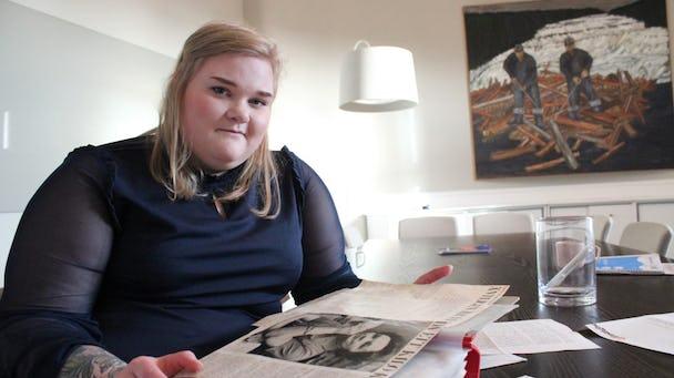 Josefin Johansson sitter vid ett bord med ett album framför sig.