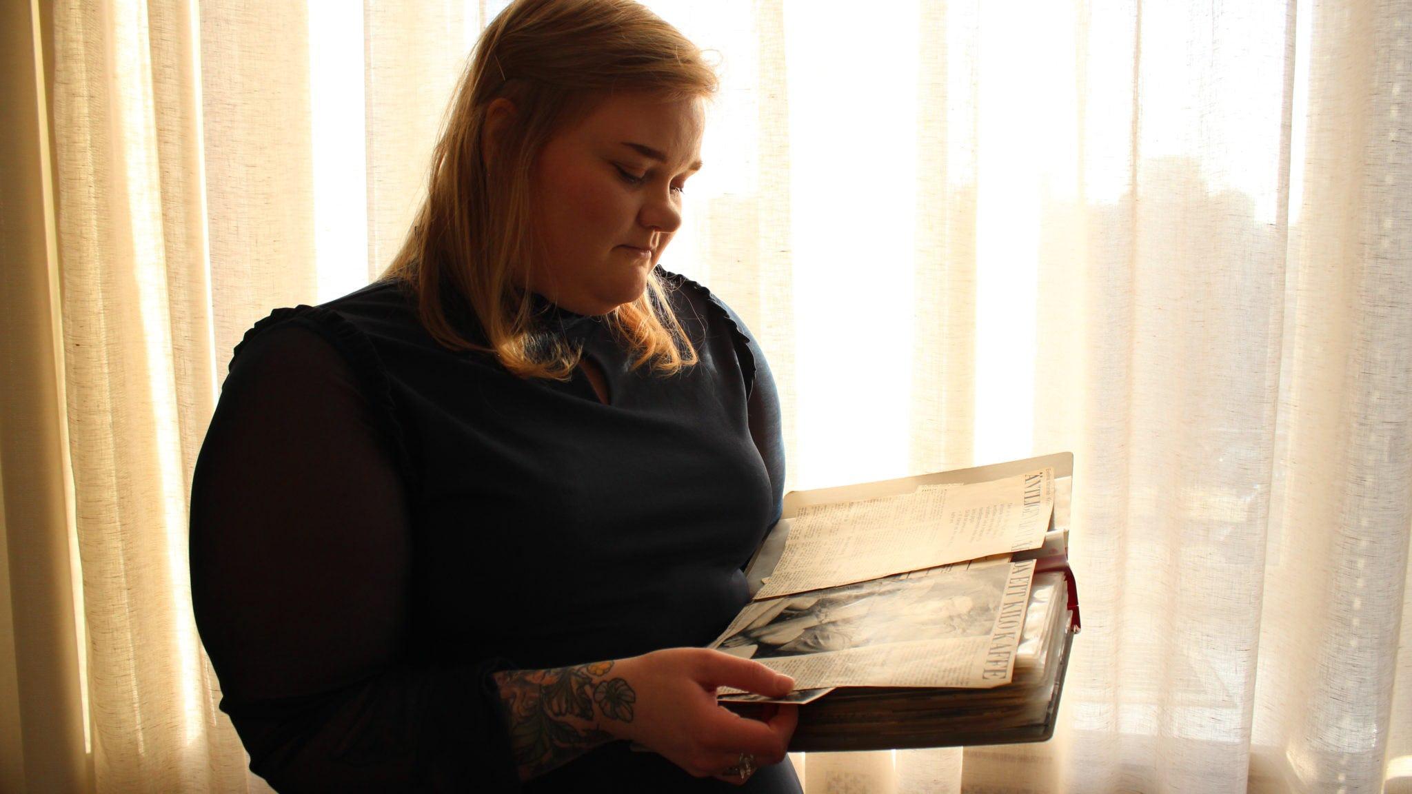 Josefin Johansson står framför ett fördraget fönster med ett album i händerna.