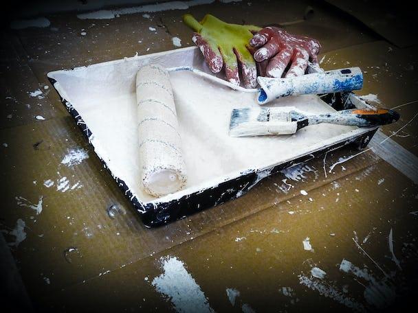 En samling målarverktyg i ett roller-tråg.