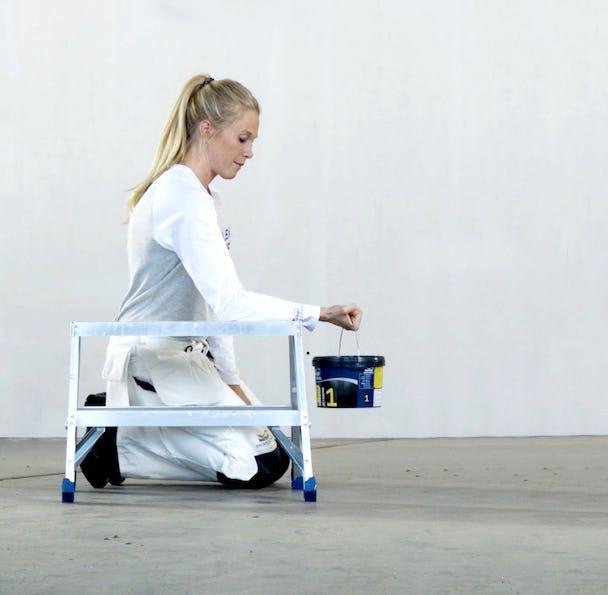 En kvinna sitter på knä på golvet med en färghink i händerna.