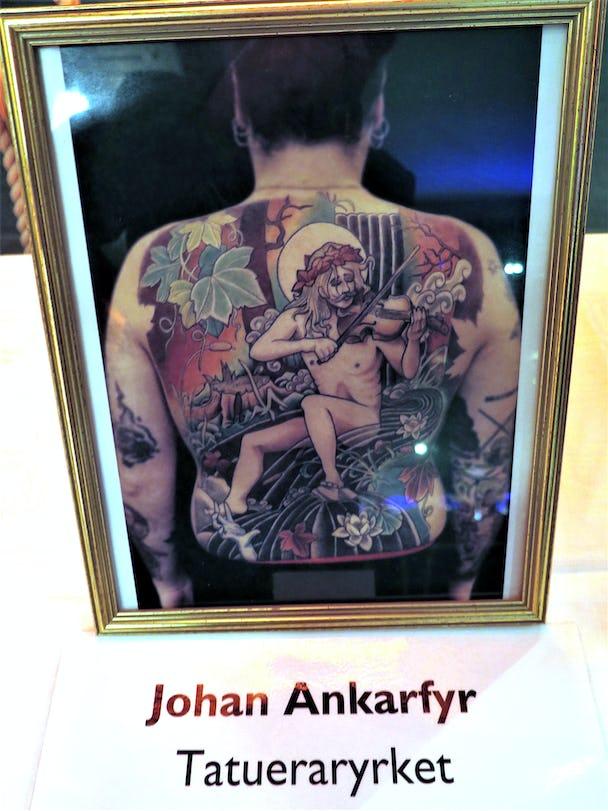 En ryggtavla med en stor tatuering föreställande en naken man som spelar fiol i ett vattendrag.