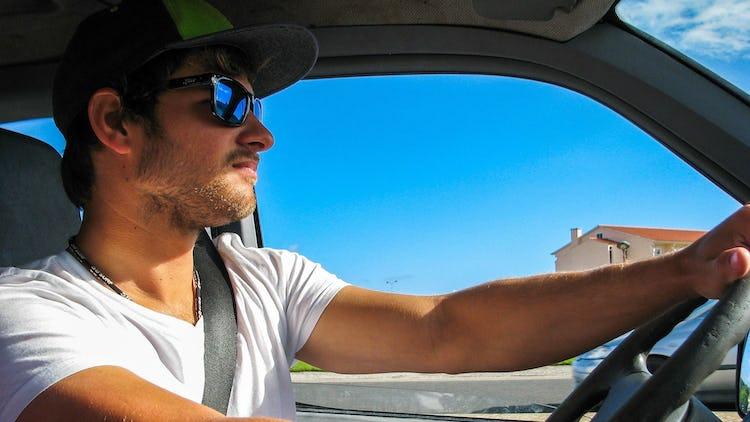 En person i solglasögon som kör bil