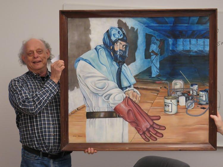 Lasse Alm håller upp en tavla