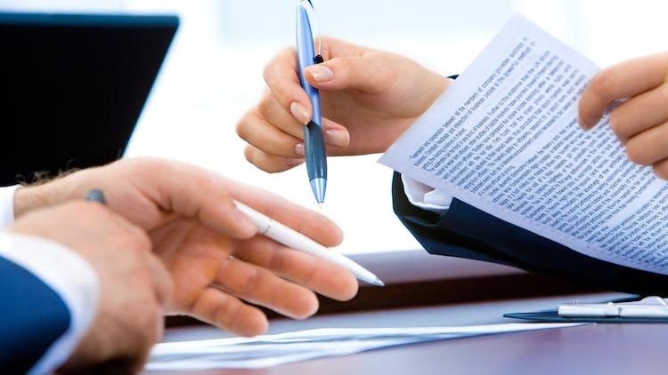 Händerna på två personer i ett möte, som håller i pennor och papper