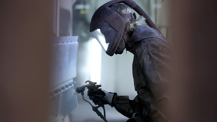 En lackerare som arbetar i skyddskläder