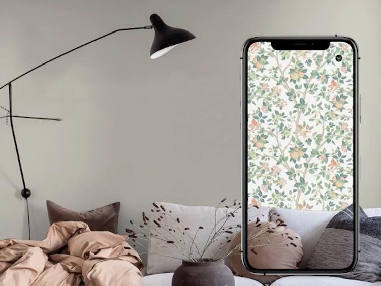 Ett vardagsrum med en överdimensionerad mobiltelefon framför, där man ser rummet med en annan tapet på väggen.
