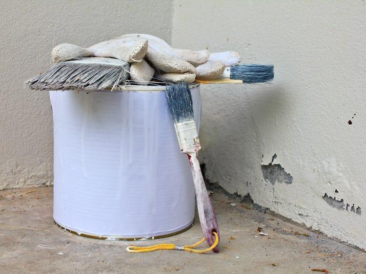 En färgburk med ett par handskar och en pensel på såt ri ett hörn