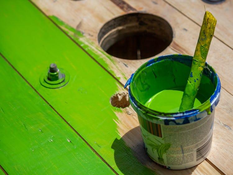 En hink med grön färg samt pensel på ett halvt målat golv