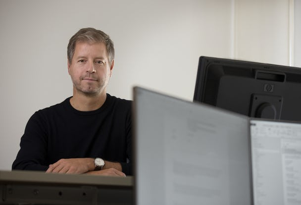 Porträttbild på Peter Sjöstrand vid en datorskärm