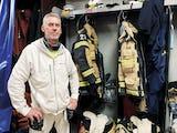 Roland Berg framför hängare med brandsmanskläder
