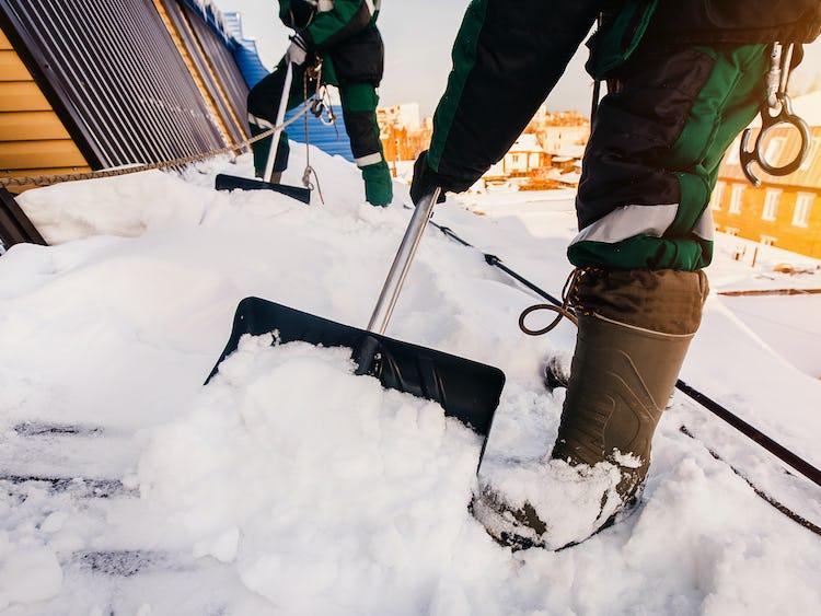 Två personer skottar snö på ett tak