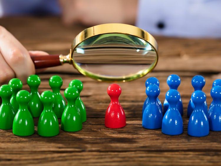 En person betraktar spelpjäser genom ett förstoringsglas. Det finns två grupper av pjäser, en grön och en blå. En ensam röd pjäs står i mitten.