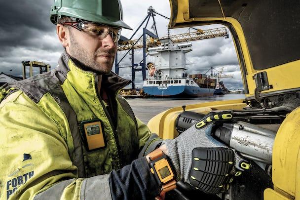 En person i skyddskläder arbetar med vibrationsklockan på handleden