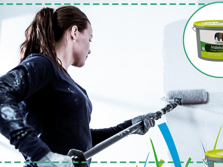 En person målar en vägg med en roller.