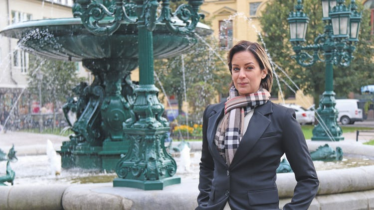 Jenny Brodin framför en fontän i en stad